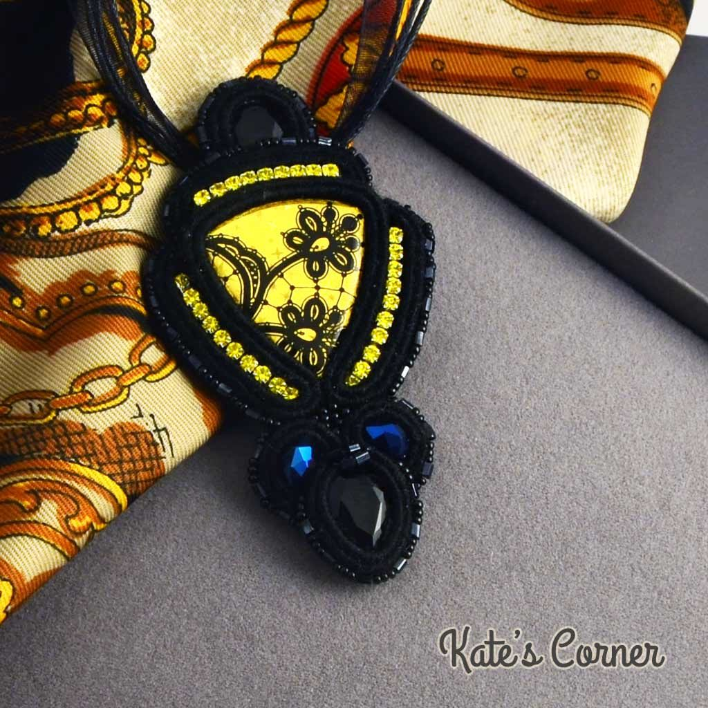 Black pendant with yellow cabochon